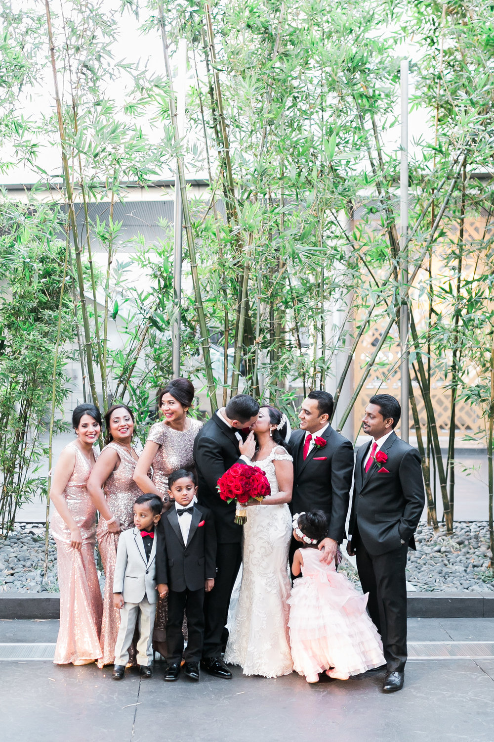 Stolen Kisses with the bridal party in front of the Mandarin Oriental Las Vegas. The flower girl hid her eyes!     Las Vegas Wedding Planner Andrea Eppolito.  www.andreaeppolitoevents.com  Photo by J.Anne Photography.  www.j-annephotography.com  As seen on The  Wedding Editorialist  Wedding Blog.