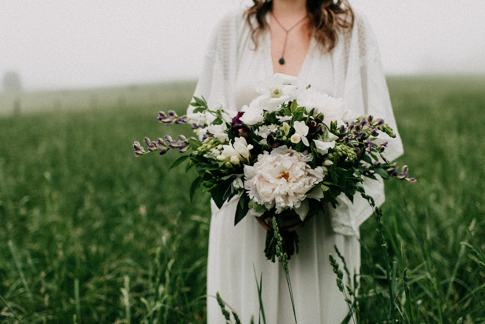White, cream, and burgundy bridal bouquet with peonies, black hero tulips, freesia, anemone and eucalyptus greens by Love & Luster Floral Design