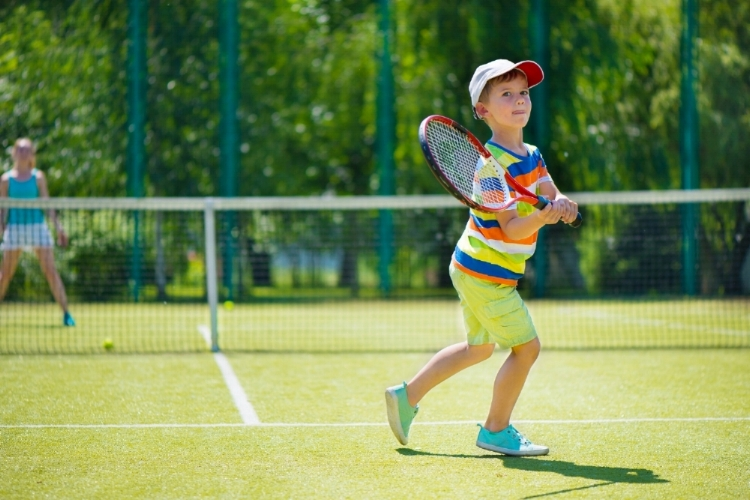 Young student playing tennis at summer camp