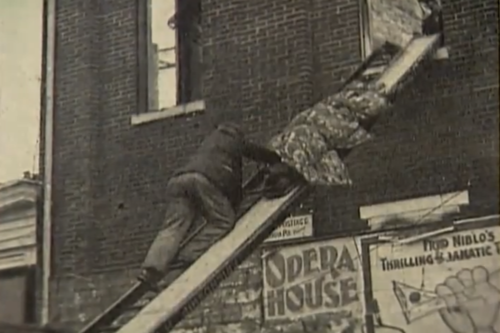 A covered body is removed from a second story window.