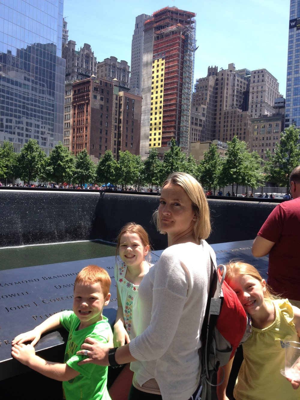 My nieces and nephews and me at the 9/11 Memorial in 2015 when they were 6, 8, and 10. As you can see, they have so little understanding of the impacts of 9/11 at that age that it did not occur to them that smiling might be inappropriate.