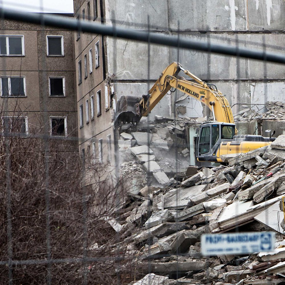 An apartment complex being demolished. The government has taken steps to reduce the amount of resources and money by demolishing buildings with little to no residence forcing people to relocate in more expensive apartments closer to the center of the city.