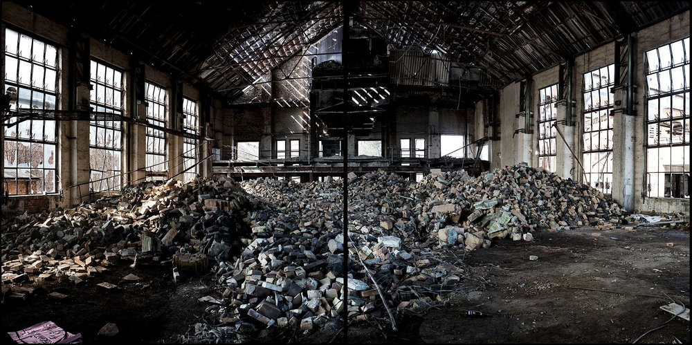 Panoramic of brick and glass piles inside of the shut down glass factory.