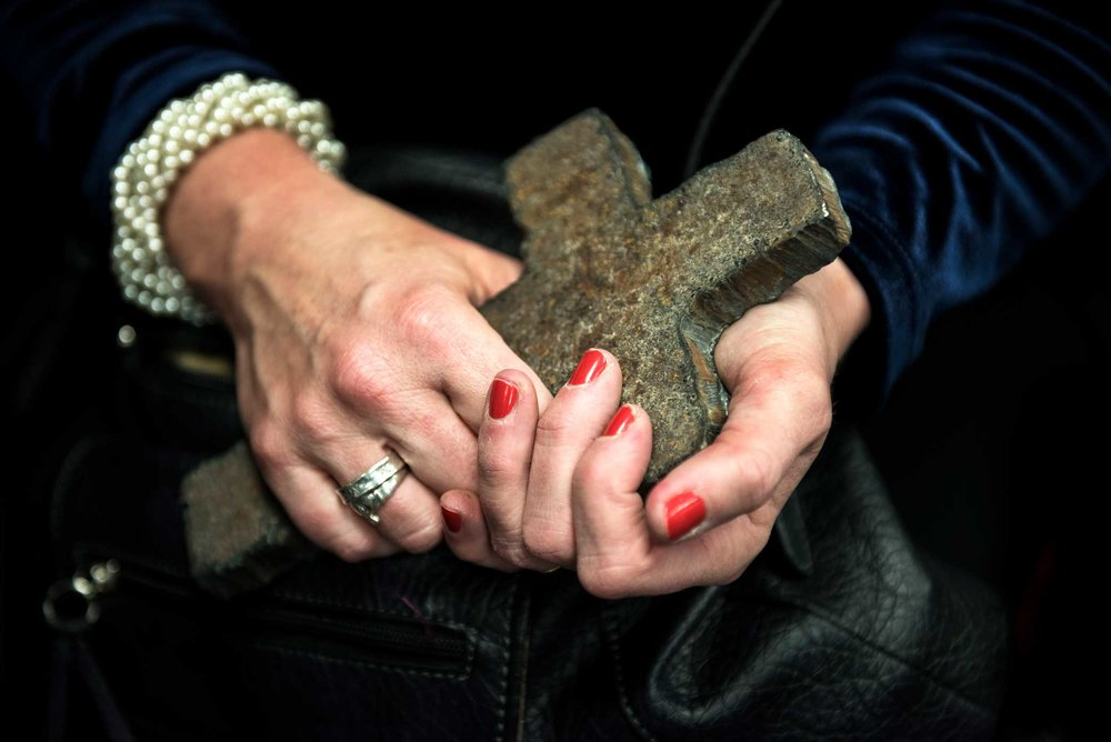 "Susan Ryan-Loback holds a cross made out of the steel from the World Trade Center. Susan volunteered with her husband, Thomas Loback, at ground zero for months, providing support to the search, rescue and recovery efforts. Thomas passed away this year from 9/11 certified pancreatic cancer. Susan suffers from COPD, asthma, chronic pneumonia and sarcoidosis. 1700+: certified deaths due to 9/11 related illnesses  ""The irony is that my lungs were much worse than his, but then one day he was diagnosed. Three weeks later he was dead."" - Susan Ryan-Loback"