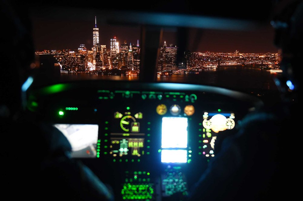 Officers with NYPD's Aviation Unit pilot their helicopter towards a stunningly lit Manhattan skyline after participating in a 5 Borough tour for National Night Out Against Crime.