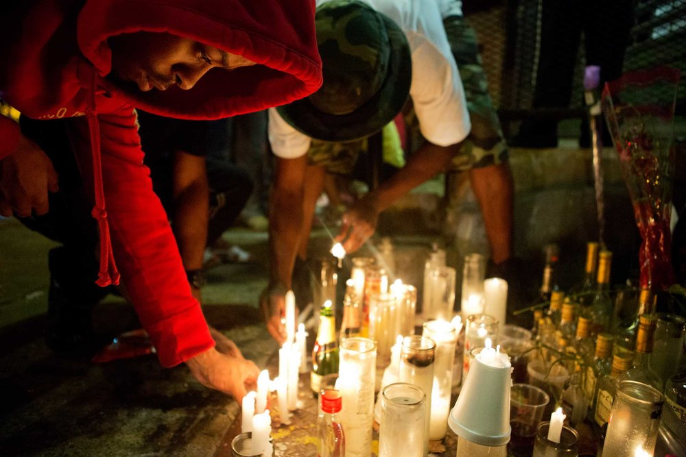 Locals light candles in memory of Olivia Brown a 23 year old who was gunned down July 30, 2013 at the Lincoln Houses at 60 East 132nd Street Harlem, New York.