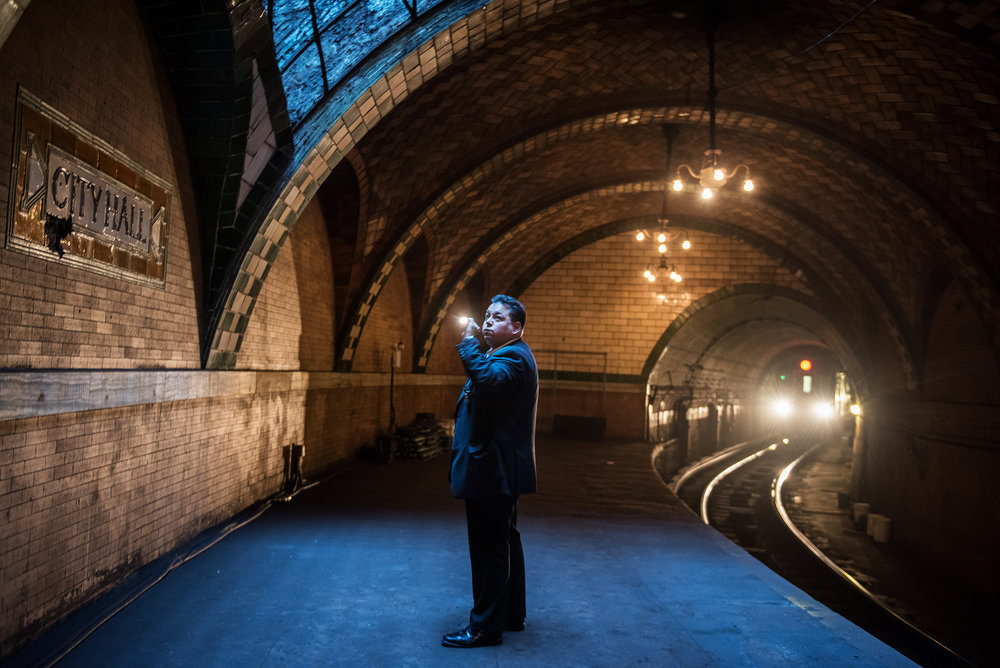 City Hall police officer inspects the inside of the City Hall Subway platform under New York City Hall in Manhattan. The City Hall subway station has been closed for more than 50 years. The 6 train passes through the station once it reaches the end of the line at City Hall Brooklyn Bridge.
