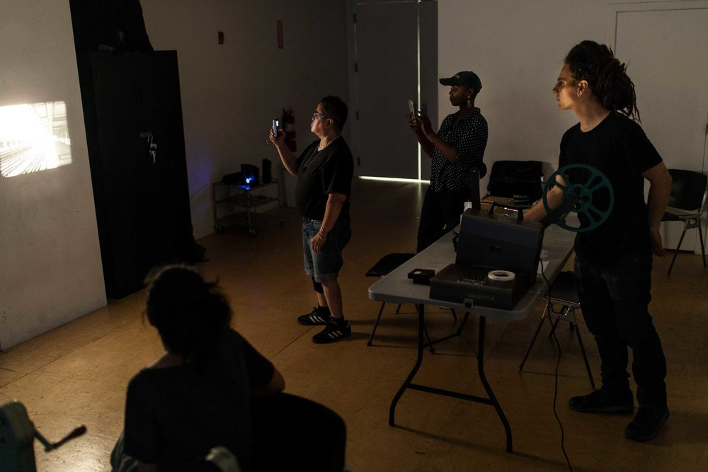 Steve Cossman, center, watch a short film on the wall with his students at the Mono No Aware workshop space in Brooklyn.