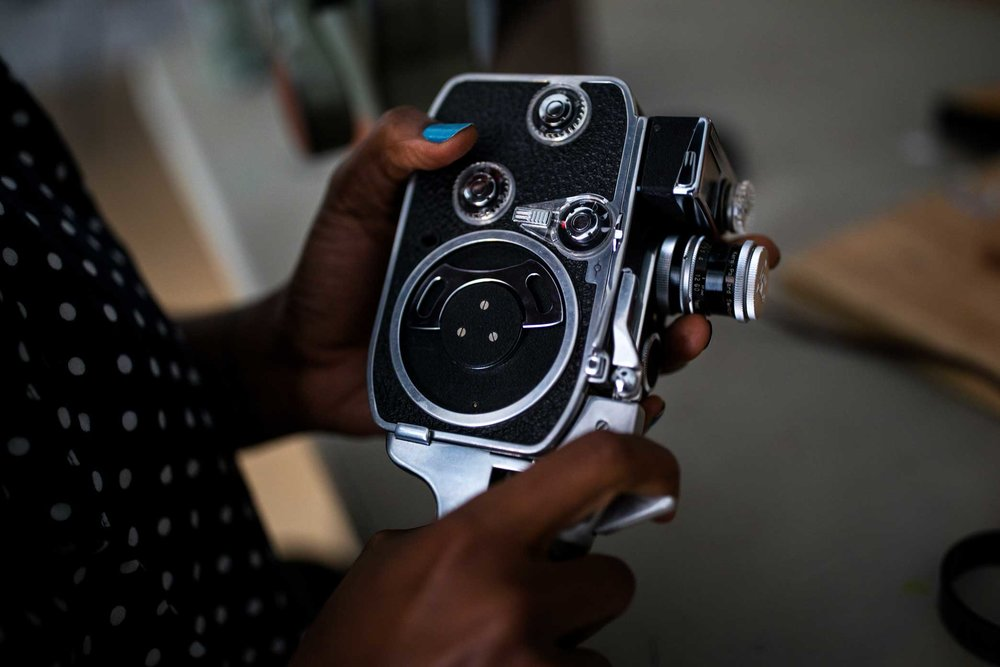 Assistant Co. Teacher, Ja' Tovia Gary, 32, examines a camera brought in from a student to be examined at the Mono No Aware workshop space in Brooklyn.