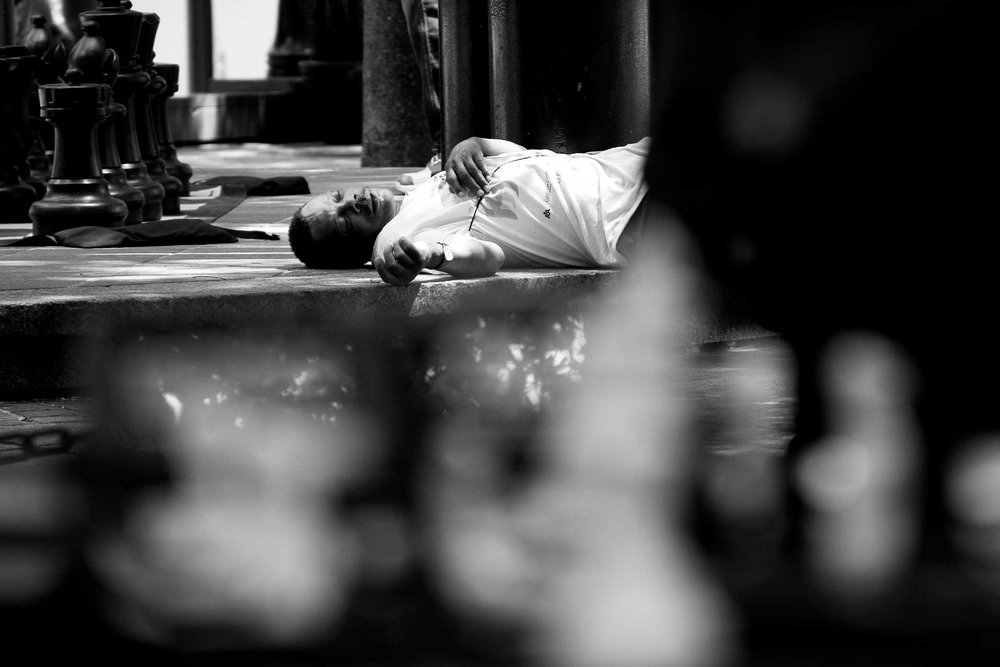 A man lies passed out in the center of the chess park. Drug and alcohol use is frequently seen in the park area.