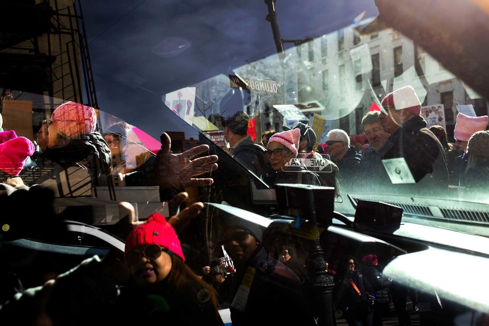 A driver yells at marchers as they weave their way through car traffic.