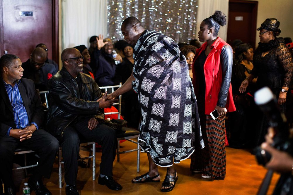 Kwabena Mensah, Mr. Mensah's father, meet and greet with guest at his sons funeral.