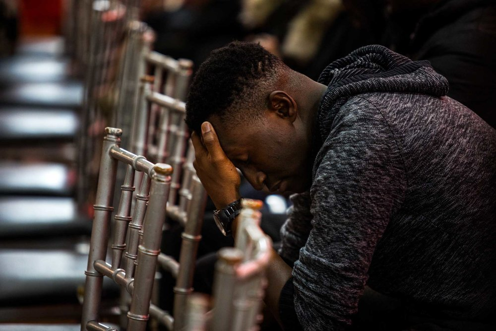 A young man lowers his head during the eulogy from Rev. Apreku.