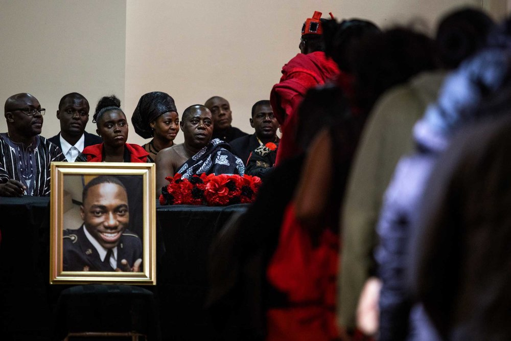 Kwabena Mensah, Mr. Mensah's father, sitting behind his son's portrait.