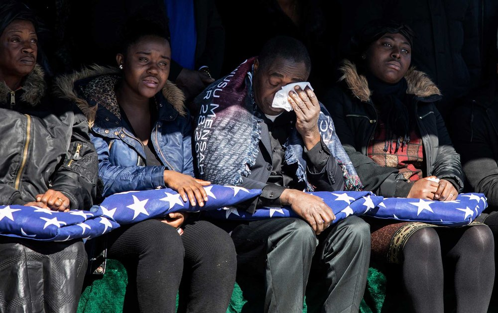 Kwbena Mensah and family watch the burial of Private Emmanuel Mensah at Woodlawn Cemetery in the Bronx.
