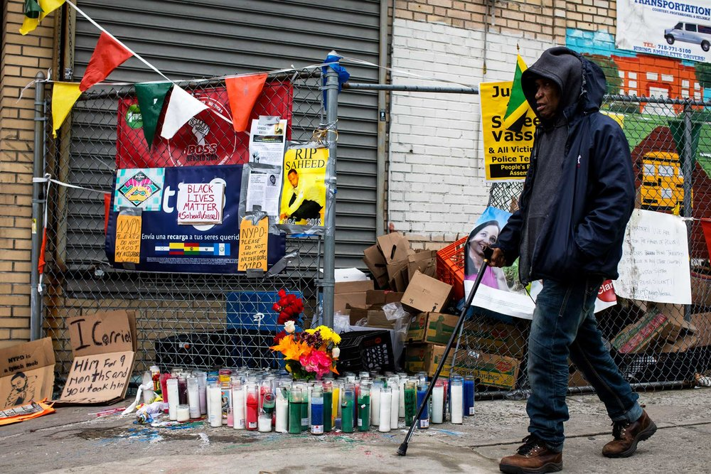 A man walk past the memorial site for Saheed Vassell in Crown Heights Brooklyn.