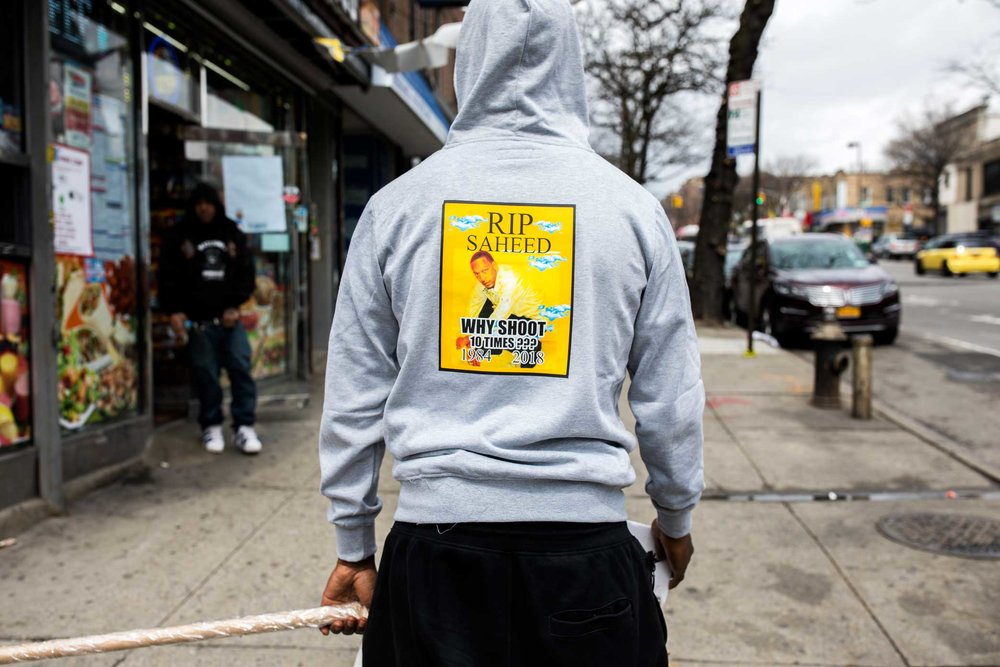 A man wearing a 'R.I.P. Saheed' shirt walking up Utica Ave carrying a 'Why Shoot' sign near the memorial site for Saheed Vassell in Crown Heights Brooklyn.
