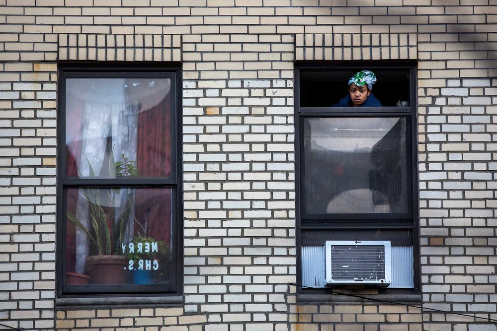 A young women watch the candle light vigil for Saheed Vassell from her window in Brooklyn.