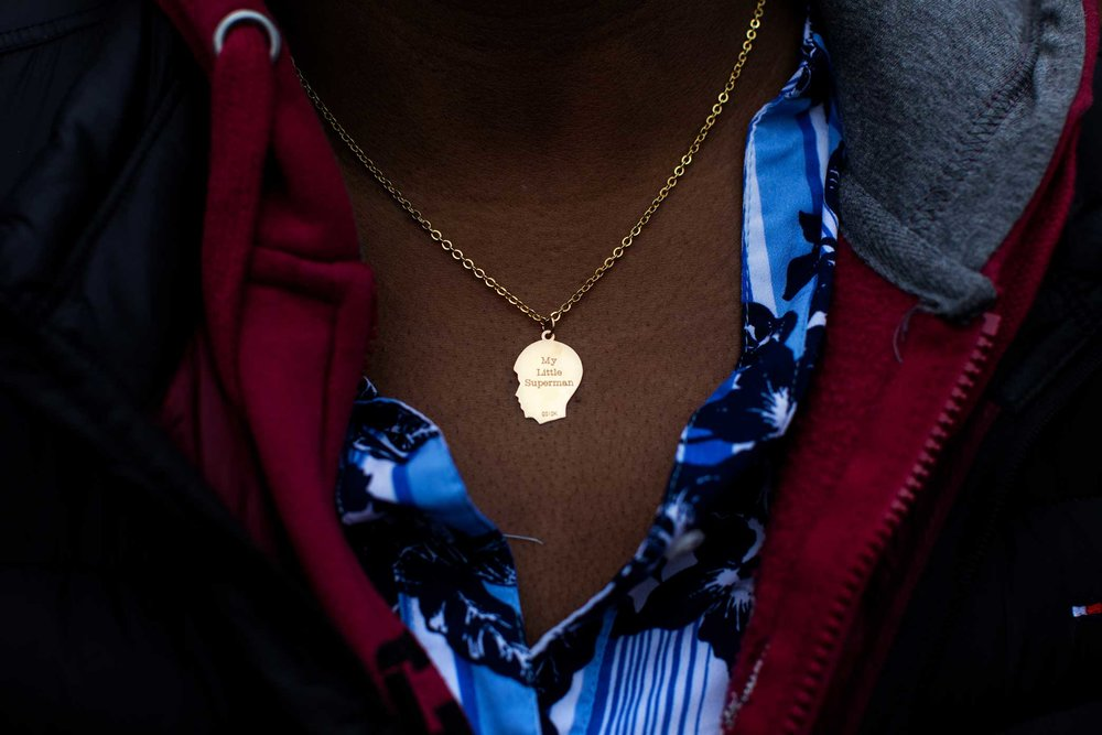 "Aricka McClinton, the mother of 6-year-old P.J. who was stabbed to death in an elevator in a housing project in East New York. She wears a charm on her necklace engraved with the words ""My Little Superman."""