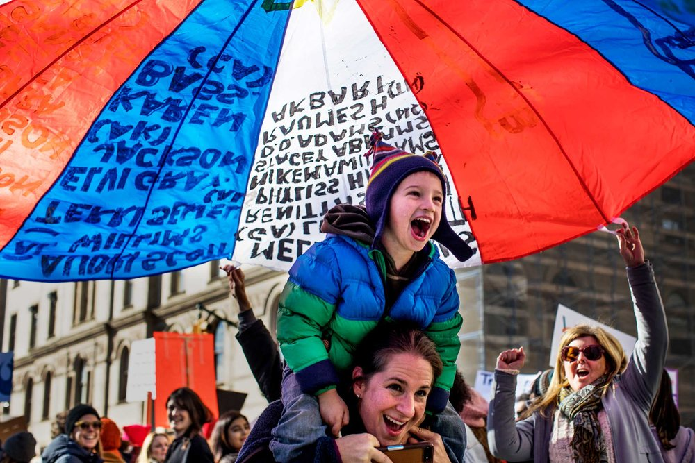 A young boy and his mother duck under a parachute with the written names of women of color who are running for political office in the U.S. during the Women's March in Manhattan, New York.