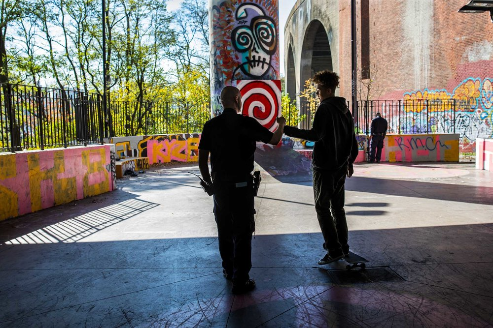 Detective Specialist Thomas W. Troppmann greet a local skater during his neighborhood patrol at Hamilton Bridge Skatepark in Upper Manhattan. Troppmann and his partner Detective Specialist Edwin A. Rodriguez are Neighborhood Coordinating Officers in the precinct who interact directly with the surrounding community in order to improve police and community relations to reduce crime.