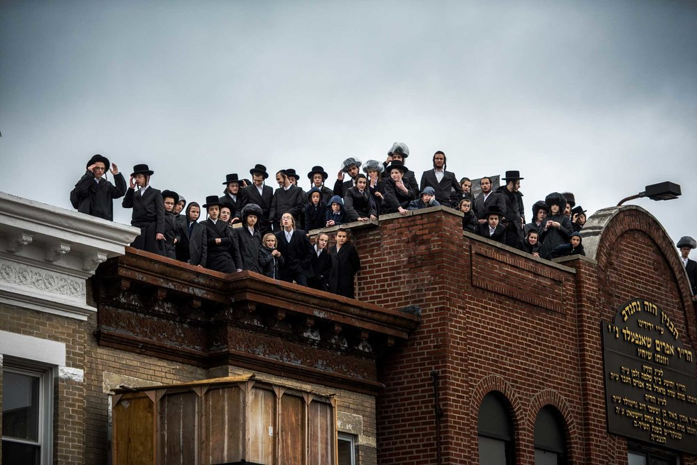 Community member watch from the roof top of their Synagogue as the New York City Fire Department work to put out flames caused by a gas explosion at a three-story building in the Borough Park section of Brooklyn.