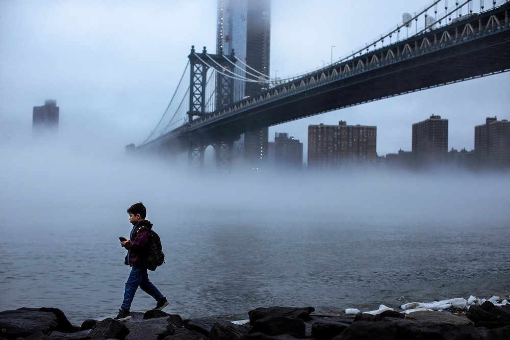 A young boy plays on the rocks as deep fog clouds the city. Brooklyn, New York.
