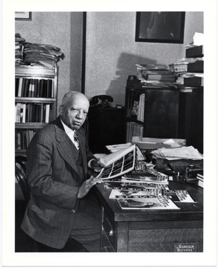 Carter G. Woodson at his desk in 1948. By Scurlock Studios. From the Smithsonian Institution archives.
