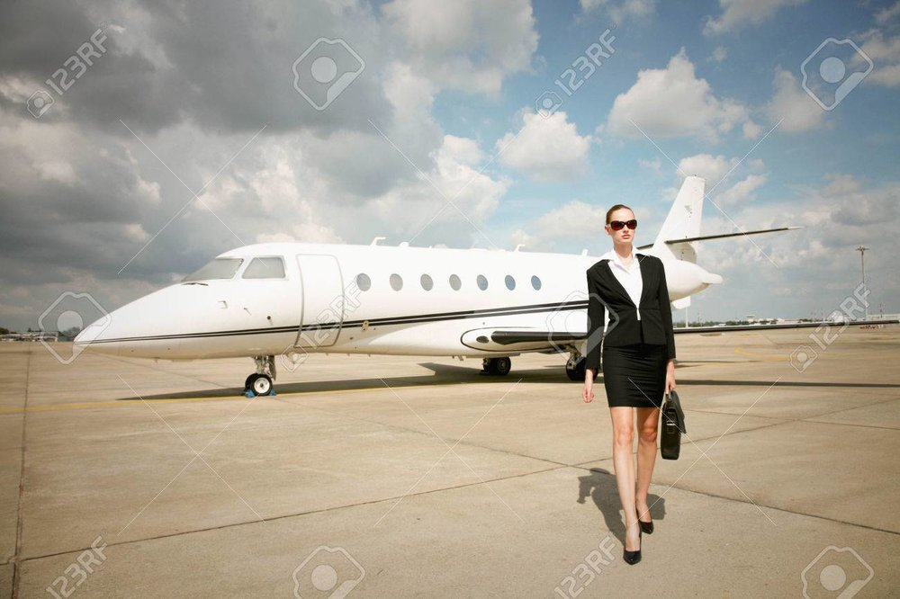 26386119-businesswoman-walking-at-runway-with-private-jet-in-the-background.jpg