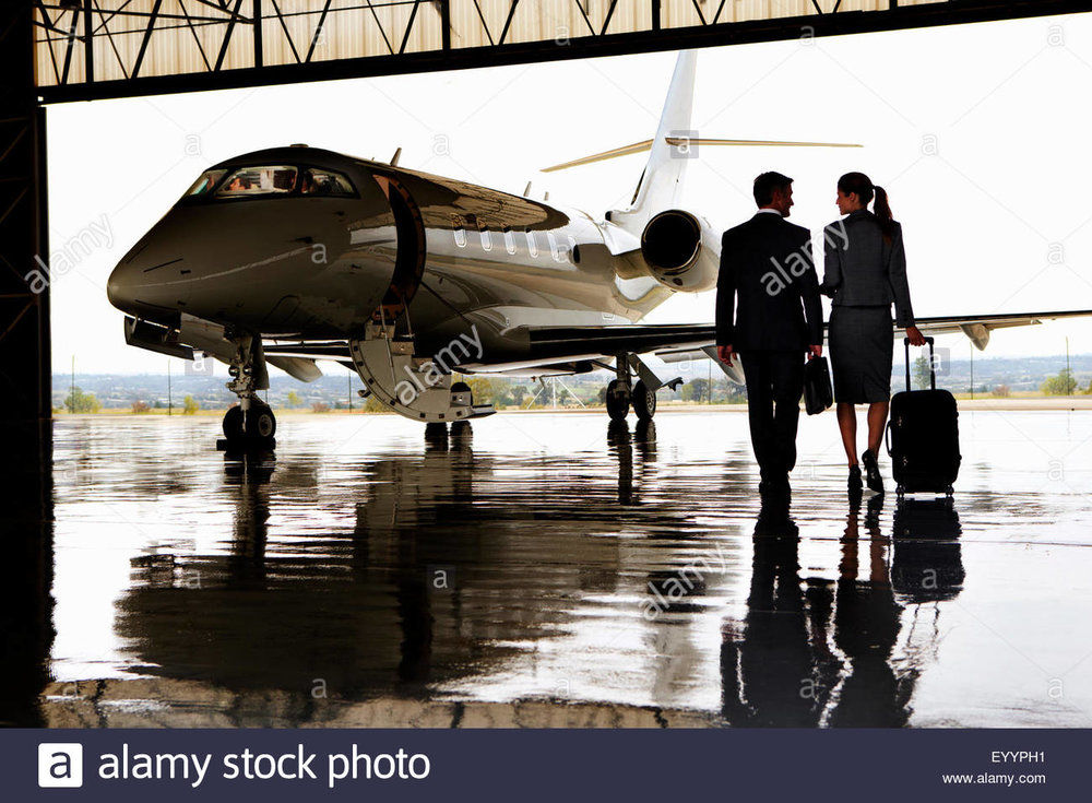 smiling-businesswoman-and-businessman-walking-toward-private-jet-EYYPH1.jpg
