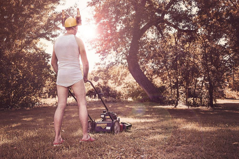 man in underwear using a lawnmower