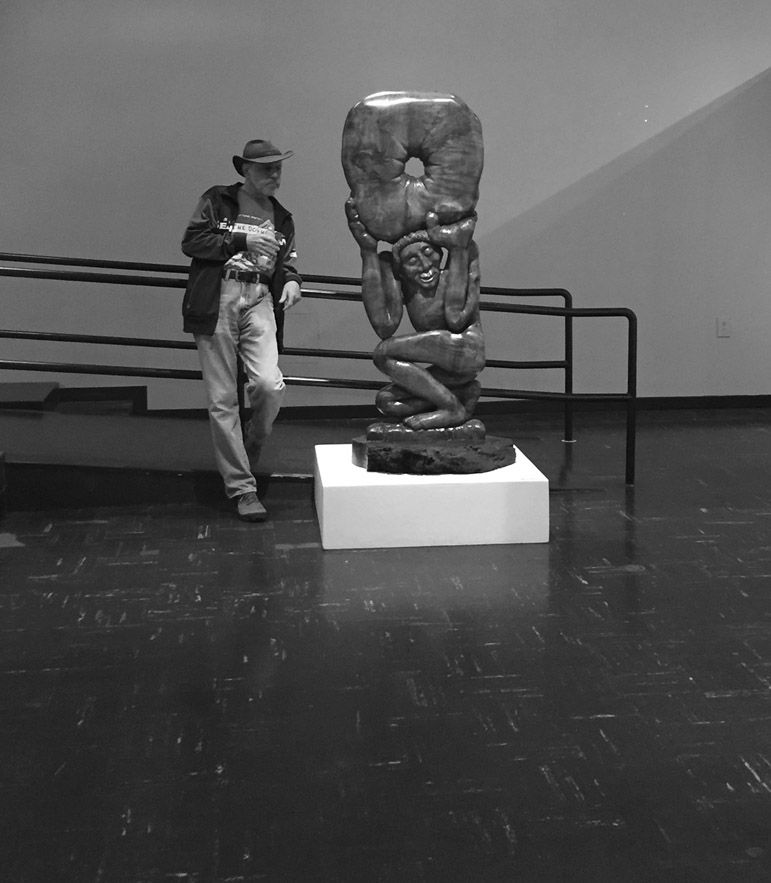 Long-time gallery associate, Stan Schiff looks at a Bill Dilley sculpture