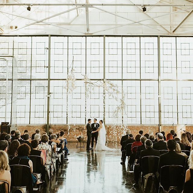 """One of my favorite moments of the day was before the ceremony even began — it was the moment Dillan first stepped into the venue and saw the ceremony installation for the first time (major wedding planner butterflies over here!! 🙋🏽♀️). This stunning ceremony site was all made possible thanks to an iconic, visionary bride unafraid to take risks, and an all-star team of creative, forward-thinking vendors who really put their hearts (and countless hours!!) into bringing this modern yet romantic design vision to life. Oh, and that ethereal, deconstructed aerial """"chuppah"""" made of thousands of floating white waxwood leaves?? That's all the artistic genius of Svenja from @chestnutandvine and her powerhouse team (DUH who else!!!) ✨ #12DaysofBeHitched . . . Videography: @goldandgumption 