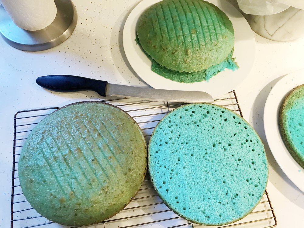 Cutting the domes off the tops of the baked cakes with a bread knife. I used the French Vanilla flavour of cake mix which had a yellowish tint to it, resulting in a greenish-blue cake exterior. Thankfully this didn't affect the colour on the inside, but if I were to bake this again I would use the White cake mix.