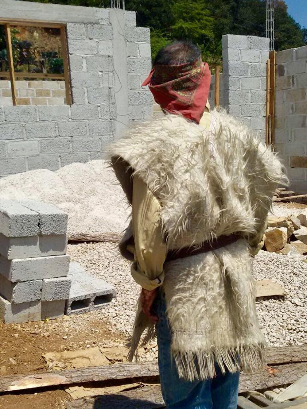 The Tzotzil man, building his house, wears white wool vest which indicates his important social status. Others wear black vests.
