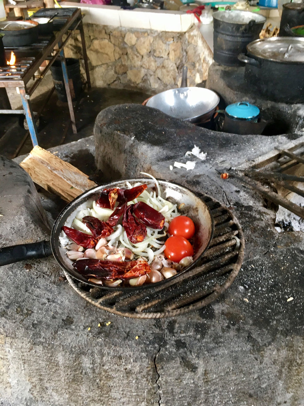 Esmeralda slowly roasts chili, garlic, onion and tomatoes on the open fire to prepare the ingredients.