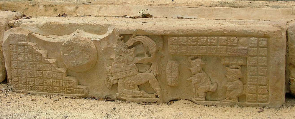Frieze from Hieroglyphic Stairway 2 in Yaxchilán shows two dwarfs in advisory role to the king during the ball game. Source:  mayaruins.com .