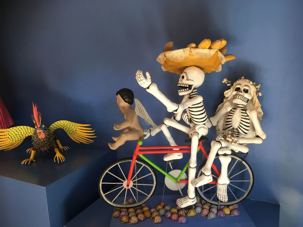 In the left corner, another  alebrije  by Angélico Jiménez. On the right side: catrines with an angel having a fun ride.