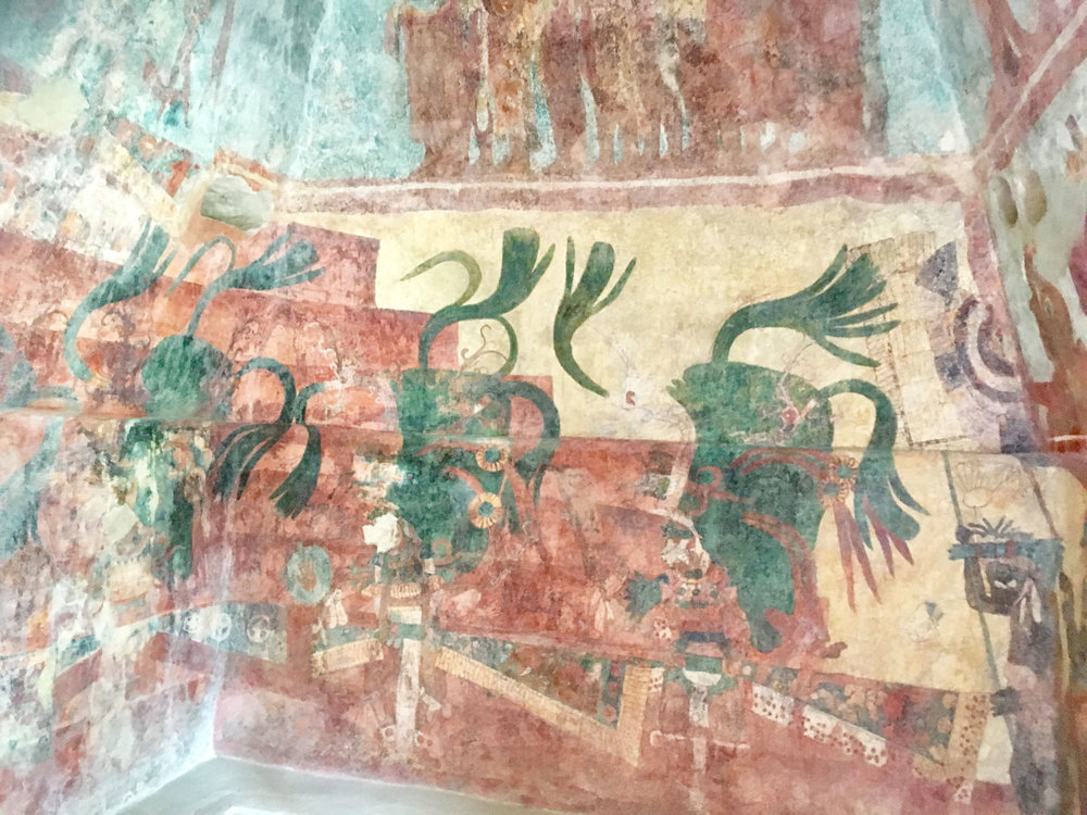 Three young heirs in the Bonampak murals, wearing tall, green, quetzal-feathered headdresses and dancer's wings.