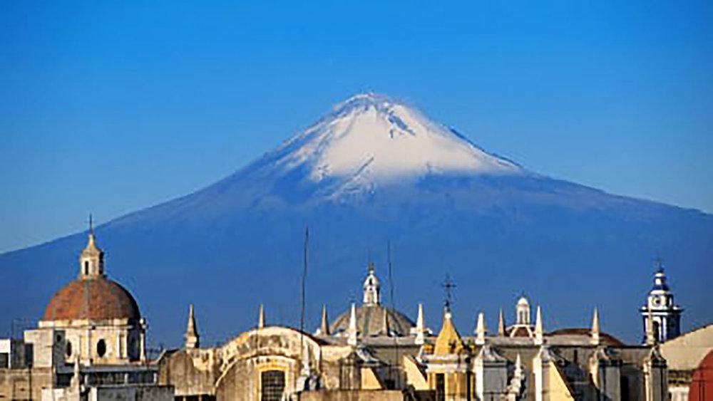 Volcano Popocatépetl makes the background of the city:  edition.cnn.com .