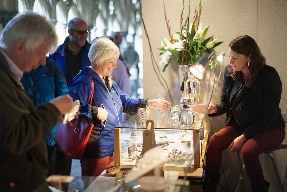 An exhibitor shows a visitor their wares