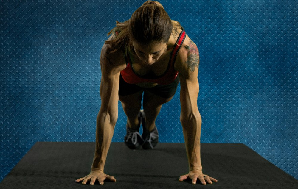 Pushup setup position: fingers forward, elbows spun mostly back, feet together, head neutral
