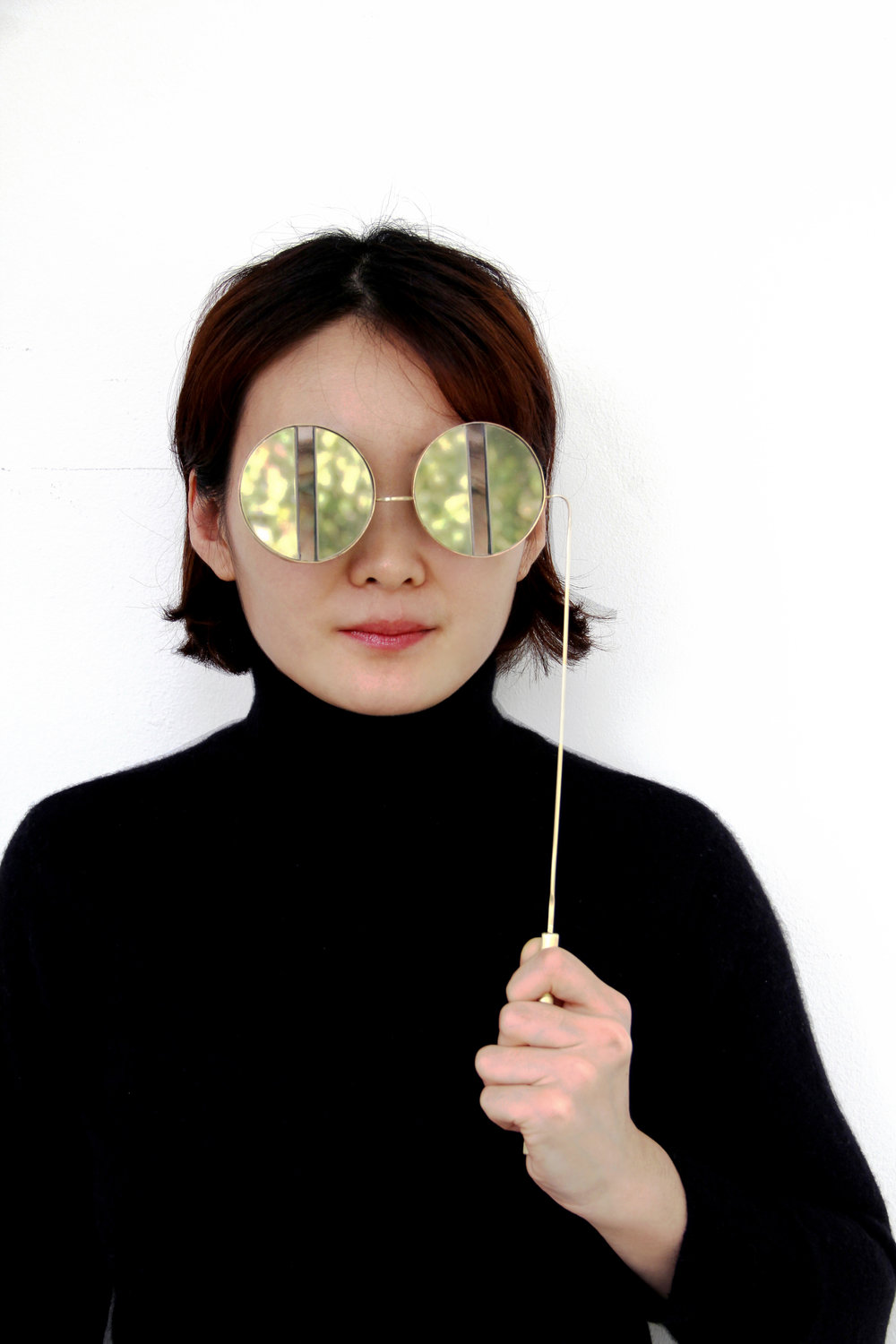 "Photography: Yi Cao. Model: Wanshu Li.  ""Deep Sight "" Mirror&Transparent acrylic, Brass, Pressed Sponge. 2016. Inspiration for this pair of glasses came from the classic theatre glasses and opera binoculars from earlier times. The size of the lenses was stretched and shaped into a stripe as seen in the piece. In addition to this the mirror-like acrylic sheet narrowed the viewpoint. The piece intentionally distorts vision, leaving the user more space and time for further pondering and reflection in the dramatic and sometimes chaotic atmosphere."