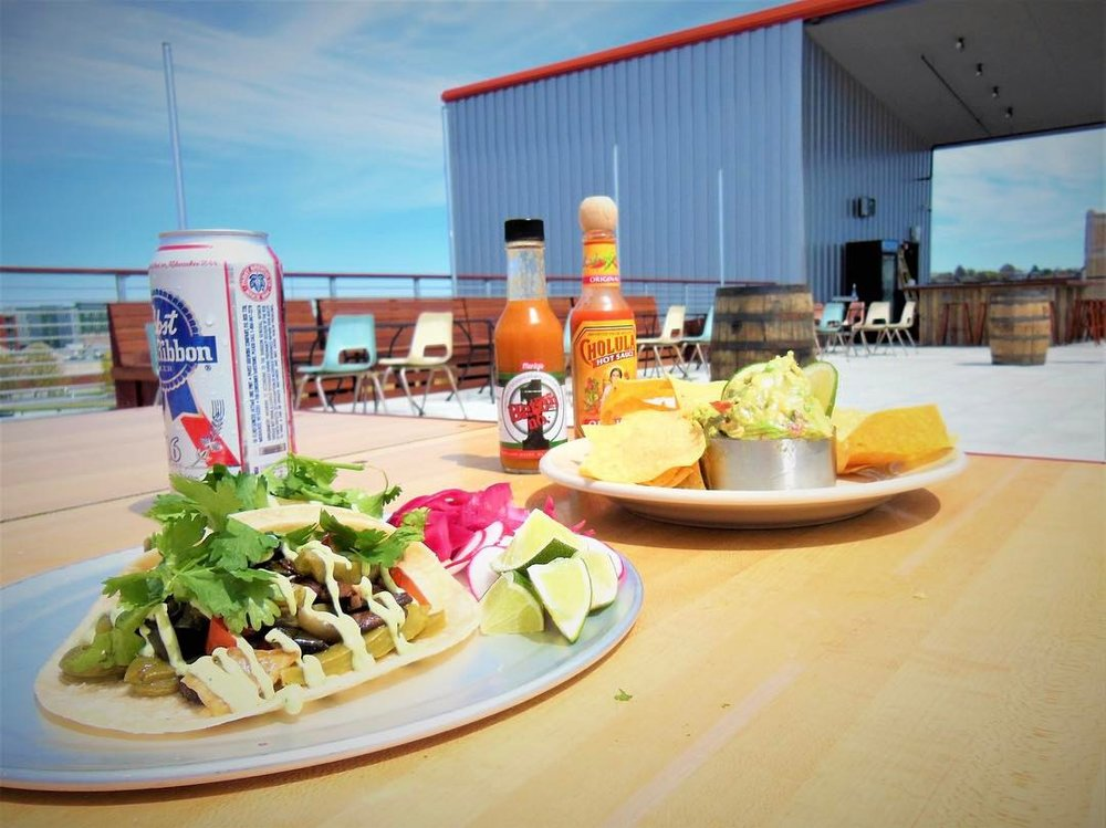 Tacos and a can of PBR on a rooftop bar