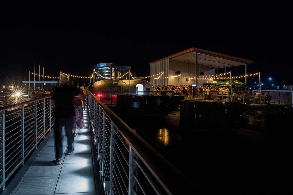 People walking a catwalk to a rooftop bar with string lights and a crowd of people