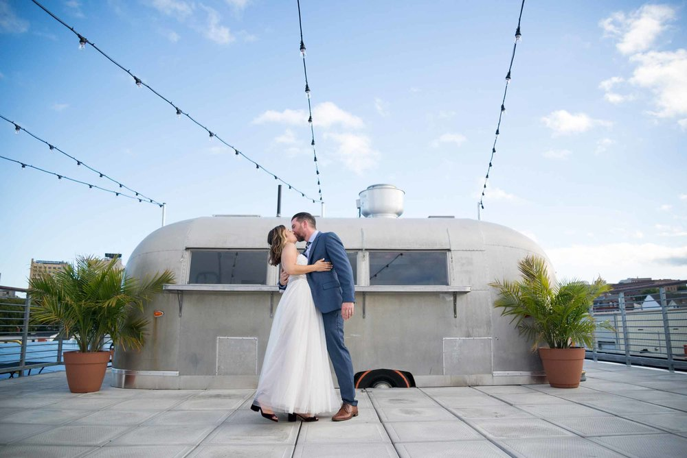 Bride and groom kissing in front of taco truck on a rooftop