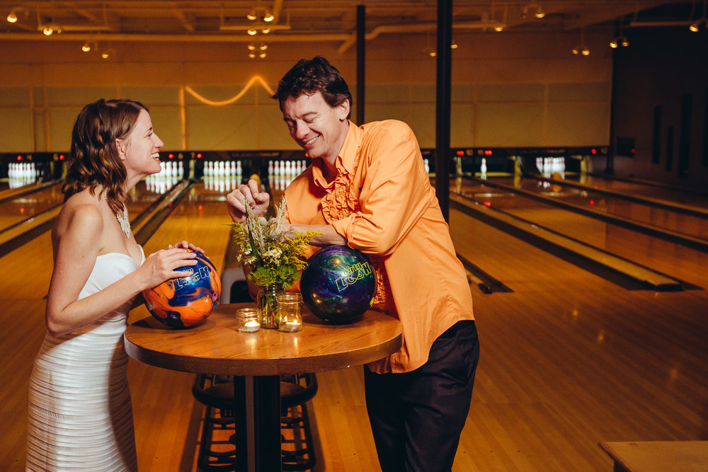Bride and groom smiling with bowling balls in front of them