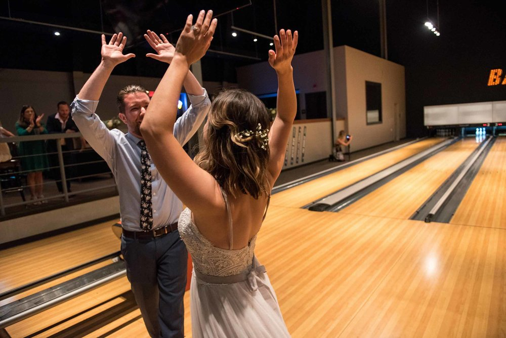 Bride and groom high-fiving one another in a bowling alley