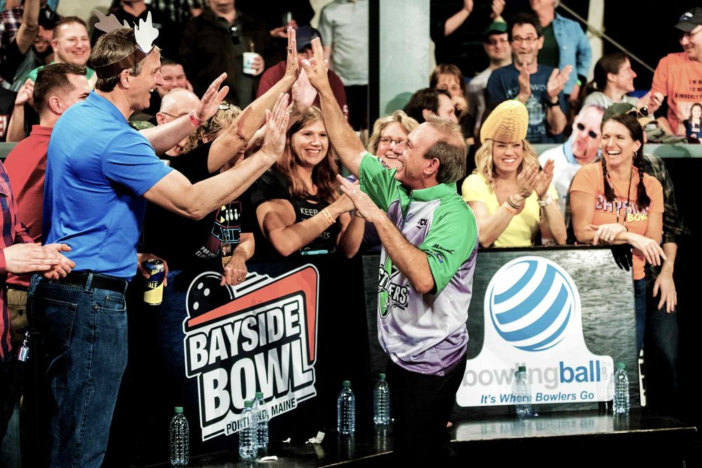 Professional bowler, Norm Duke, high-fiving a crowd at Bayside Bowl