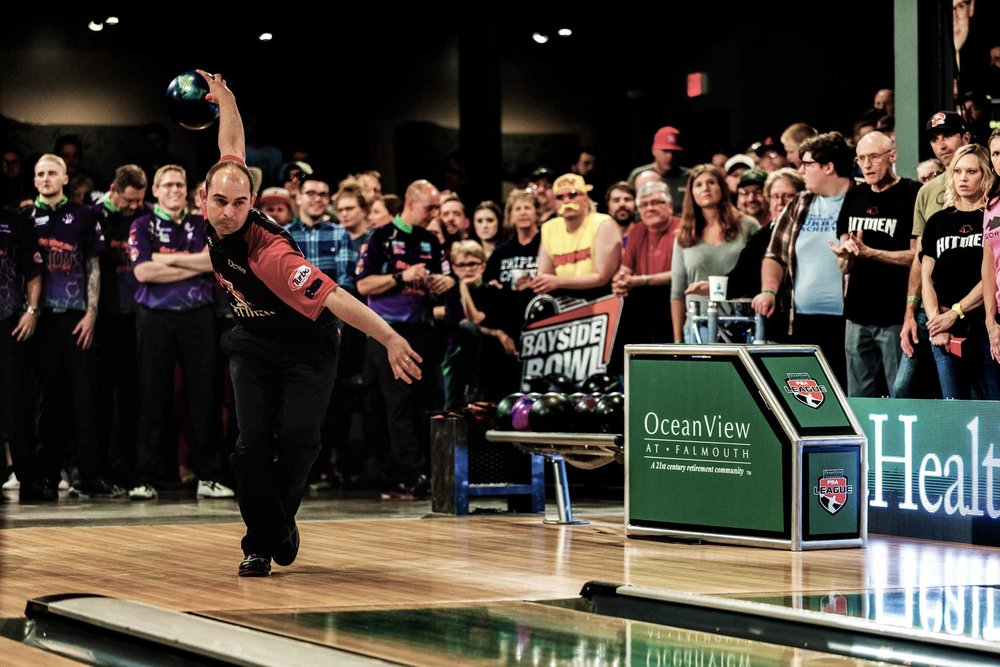 Professional bowler getting ready to throw the ball with team and crowd behind him